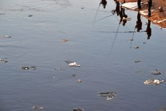 Reflection of fishermen in dirty river water with swimming melting ice in spring time. stock photos