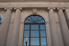 Reflection of flags at the Pennington County Courthouse in Rapid City South Dakota. Columns and flags at the historic Pennington County Courthouse in Rapid City royalty free stock photo