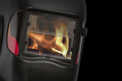 Reflection of the flame in the glass protective mask Stock Image