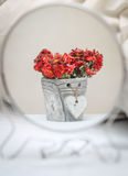 Reflection of flowers in the mirror. Reflection of flowers in a pot with a heart in a round mirror standing on a white bed royalty free stock photos