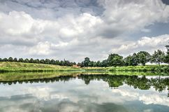 Reflection in fortified town Leusden. Dramatic cloudy sky reflecting in the calm water of one of the moats surrounding the fortified town of Leusden, The stock images