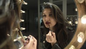 Reflection of girl applying her make-up. Brunette young woman putting lipstick stock footage