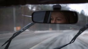 Reflection of girl driving car in rearview mirror stock video footage