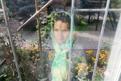 Reflection of a girl in a scarf in a window. royalty free stock photo