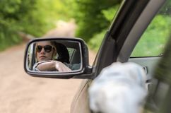 Reflection of a girl sitting in the car in a car mirror.  Royalty Free Stock Image