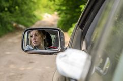 Reflection of a girl sitting in the car in a car mirror.  Royalty Free Stock Photo
