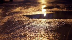 Reflection of glare in a puddle and wet asphalt. At night stock video