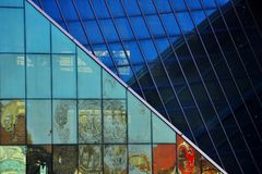 Reflection on the glass walls. Refleciton on the glass wall of a modern building, colorful walls and geometry on the surface was atractive for citylife also blue stock images