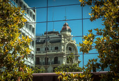 Reflection in Granada. A beaux artes style building reflected in the glass of a modern building Royalty Free Stock Photos