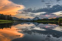 Reflection of Grand Tetons in Jackson Lake at sunset with beautiful clouds. Reflection of Grand Tetons in Jackson Lake at sunset with beautiful orange clouds royalty free stock photo