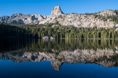 Reflection of a granite mountain peak and cliffs in a calm alpine lake under a perfect blue sky. Crystal Crag in California`s Sierra Nevada mountains is royalty free stock images
