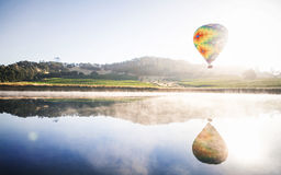 Reflection of Green Yellow and Red Hot Air Balloon in Lake Royalty Free Stock Image