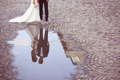 Reflection of a groom and bride in the water Royalty Free Stock Image