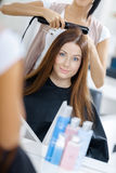 Reflection of hair stylist doing hairdo for woman Stock Photo