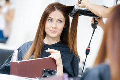 Reflection of hairdresser doing hairdo for woman Stock Photos