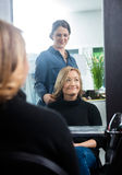 Reflection Of Hairdresser Setting Client's Hair Royalty Free Stock Photography