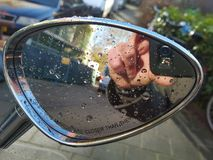 Reflection of hand with camera in rear view mirror Stock Photos
