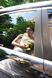 Reflection of happy bride in wedding limo window royalty free stock photography