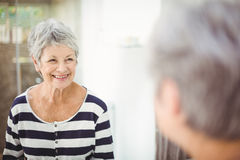 Reflection of happy senior woman on mirror. In bathroom royalty free stock image
