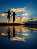 Reflection of Happy of two women jumping and sunset silhouette Stock Photos