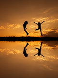 Reflection of Happy of two women jumping and sunset silhouette Stock Images