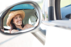 Reflection of happy woman in rearview mirror of car Stock Photo