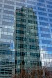 Reflection of highrise tower in the windows of another tower at La Defense busines district, paris, france. Eflection of modern highrise tower mirrored in the Royalty Free Stock Images