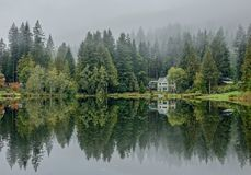 Reflection of a house on the edge of a lake on a foggy day royalty free stock photos