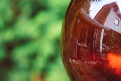 Reflection of House in garden glass ball stock image