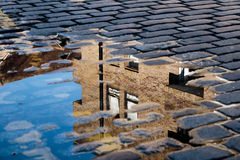 Reflection of House in Puddle. Cobblestone with reflection of house in puddle after rain stock photography