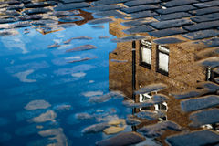 Reflection of House in Puddle. Cobblestone with reflection of house in puddle after rain royalty free stock photography