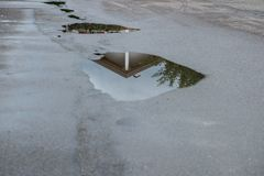 Reflection of a house in a water puddle after a rain storm stock image