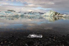 Reflection of ice cubes with black gravel and small ice cube foreground at  Jokulsarlon Glacier Lagoon Royalty Free Stock Image