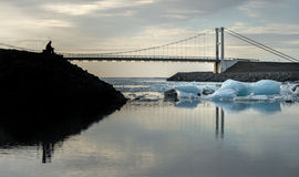 Reflection of ice cubes and hanging bridge with silhouette man foreground at  Jokulsarlon Glacier Lagoon Stock Photo