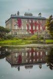 Reflection of an Irish mansion. Swans swimming in a lake beside an Irish mansion royalty free stock image