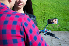 Reflection of kissing couple in motorbike mirror. Reflection of young kissing couple in motorbike mirror stock photos