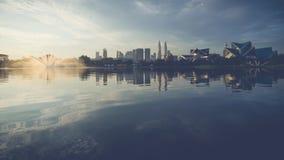 Reflection of Kuala Lumpur in lake Titiwangsa. KUALA LUMPUR, MALAYSIA - MARCH 6, 2015: Sunrise view of Kuala Lumpur at Lake Titiwangsa, Malaysia.The lake is Royalty Free Stock Photo