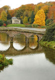 Reflection in the lake. England in the autumn. Golden trees and an 18th century bridge against a still lake Royalty Free Stock Image