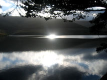 Reflection on lake. Sun setting over lake in wales Royalty Free Stock Image