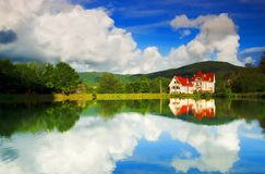 Reflection in lake. Red house situated beside the small lake in Ukrainian mountains Royalty Free Stock Photos