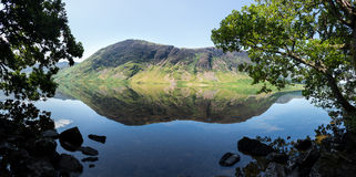 Reflection on Lake District hills in Crummock. Mirror like reflection of the Lake District hills surrounding Crummock Water framed by the trees on the lakeside Royalty Free Stock Photo