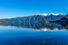 Reflection in Lake Hauroko, New Zealand. Reflection of snowy mountains in Lake Hauroko in the Southern Scenic Route, New Zealand stock photo