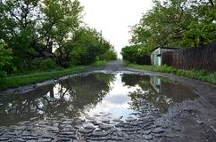 Reflection in a large puddle formed by rains. Reflection in a large puddle formed by rains on a stone road royalty free stock image