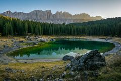 Reflection of Latemar in the clear water of Lake Carezza Karersee in Dolomite Alps, Trentino Alto Adige, South Tirol, Italy royalty free stock images