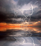 Reflection of lightning in the water. Reflection of lightning and sunset in the water Royalty Free Stock Photo