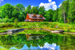 Reflection of a log cabin in the near by pond HDR Royalty Free Stock Photos