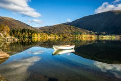 Autumn Landscape with A Lone Boat, Mountains, Colorful Trees and Blue Sky Reflected in Lake stock photography