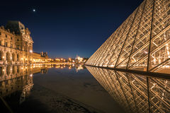 Reflection of Louvre pyramid shines at dusk. Royalty Free Stock Photography