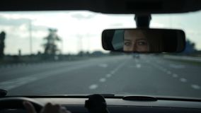 Reflection of lovely woman in car rear-view mirror stock footage