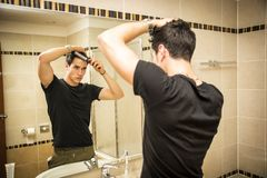 Reflection of Man Bushing Hair in Mirror. Reflection of Young Man Bushing Hair in Bathroom Mirror Getting Ready to Go Out Royalty Free Stock Photo